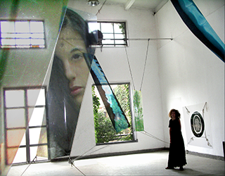 Barbara Rosenthal standing in the Pickled Art Centre, Beijing, dwarfed by her enormous, delicate, wafting installation.